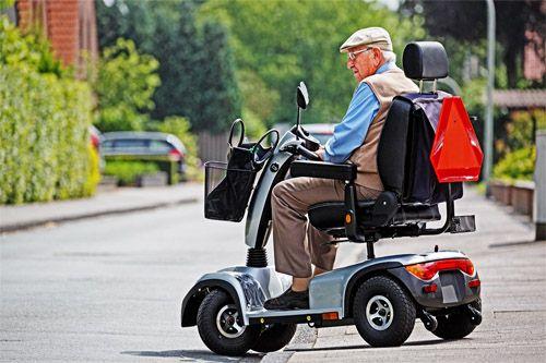Älterer Herr fährt auf einem Elektromobil die Straße entlang