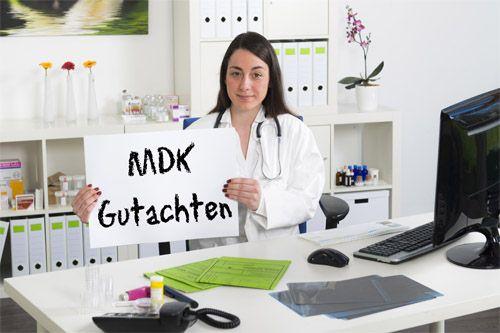 Frau hält ein Schild hoch mit dem Satz MDK-Begutachtung