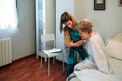 Ältere Frau wird von einer Pflegedienstmitarbeiterin betreut
